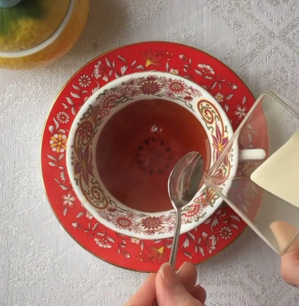 red and white Wedgwood teacup and saucer on a white tablecloth. A person is holding a spoon and about to pour in cream