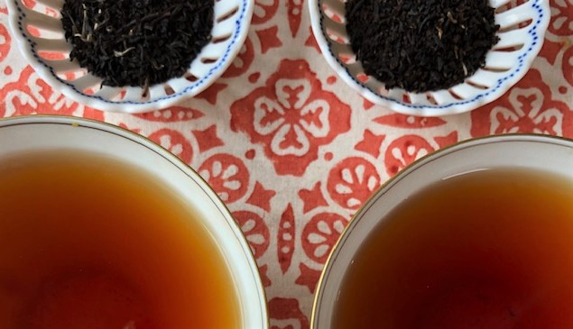 two cups of black tea with the dry tea leaves above them on an orange and white tablecloth